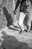 Jeune femme adulte marchant vers le haut des escaliers et du mur de briques sous l'escroquerie images libres de droits