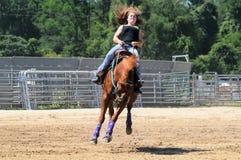 Jeune femme adulte montant un cheval s'opposant Photographie stock libre de droits