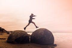 Jeune femme adulte sautant sur des rochers de Moeraki, île du sud nouvelle photographie stock