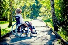Jeune femme adulte sur le fauteuil roulant en parc Image libre de droits