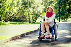 Jeune femme adulte sur le fauteuil roulant en parc Photographie stock libre de droits