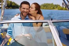 Jeune femme affectueuse embrassant le mari naviguant un bateau Image libre de droits