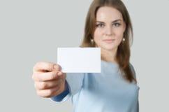 Jeune femme affichant la carte de visite professionnelle vierge de visite Photographie stock libre de droits