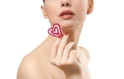 Jeune femme affichant la sucrerie en forme de coeur. Photo stock