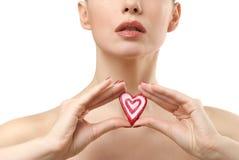 Jeune femme affichant la sucrerie en forme de coeur. Images libres de droits