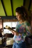 Jeune femme affichant un livre photographie stock libre de droits
