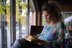 Jeune femme affichant un livre photos stock