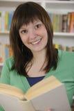 Jeune femme affichant un livre dans la bibliothèque Image libre de droits