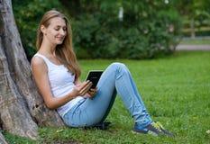 Jeune femme affichant un livre en stationnement Photo libre de droits