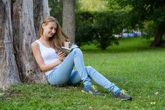 Jeune femme affichant un livre en stationnement Image stock