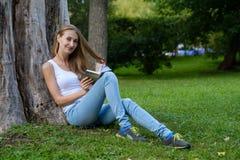 Jeune femme affichant un livre en stationnement Photographie stock libre de droits