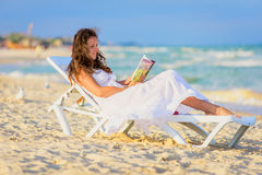 Jeune femme affichant un livre à la plage Photos stock