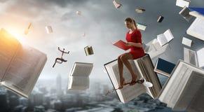 Jeune femme affichant un livre Media m?lang? image stock