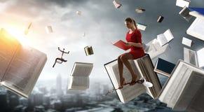 Jeune femme affichant un livre Media m?lang? image libre de droits