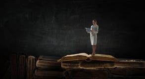 Jeune femme affichant un livre Media m?lang? photo libre de droits