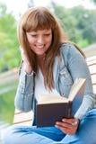 Jeune femme affichant un livre se reposant sur le banc Photos libres de droits
