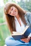 Jeune femme affichant un livre se reposant sur le banc Photographie stock