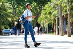 Jeune femme africaine attirante intégrale marchant avec le sac et le téléphone portable photographie stock libre de droits