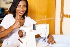 Jeune femme africaine cousant dans son studio Photos libres de droits