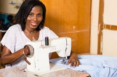 Jeune femme africaine cousant dans son studio Image stock