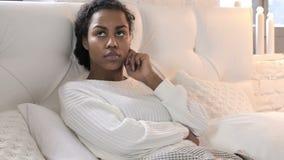 Jeune femme africaine de pensée songeuse s'étendant dans le lit banque de vidéos