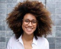 Jeune femme africaine de sourire avec Afro et des verres Photographie stock libre de droits