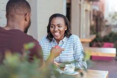Jeune femme africaine de sourire obtenant un cadeau de son ami Photographie stock