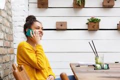Jeune femme africaine de sourire parlant au téléphone portable au café Images stock