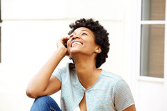 Jeune femme africaine de sourire s'asseyant dehors et recherchant Image stock