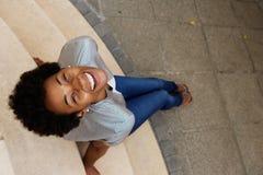 Jeune femme africaine de sourire s'asseyant sur des étapes et recherchant Images stock
