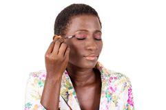 Jeune femme africaine faisant son maquillage Photographie stock