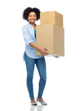 Jeune femme africaine heureuse avec des boîtes de colis images stock