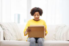 Jeune femme africaine heureuse avec la boîte de colis à la maison Images stock