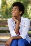 Jeune femme africaine heureuse s'asseyant sur un banc de parc Photos libres de droits