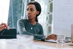 Jeune femme africaine lors de la réunion d'affaires image stock