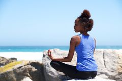 Jeune femme africaine s'asseyant à la plage dans la pose de yoga Photographie stock