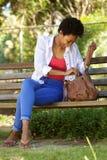 Jeune femme africaine s'asseyant sur un banc de parc avec un sac Photos libres de droits