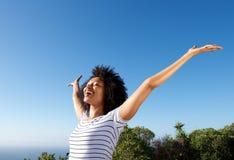 Jeune femme africaine se tenant dehors avec des bras augmentés et rire photos stock