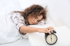 Jeune femme afro-américaine arrêtant le réveil à la maison image libre de droits