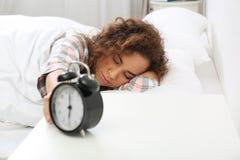 Jeune femme afro-américaine arrêtant le réveil photo stock