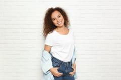Jeune femme afro-américaine avec le beau visage près du mur de briques image libre de droits