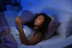 Jeune femme afro-américaine avec le téléphone portable la nuit photo stock