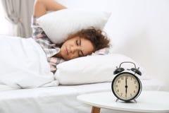 Jeune femme afro-américaine couvrant des oreilles d'oreillers tout en se cachant du réveil à la maison photos stock