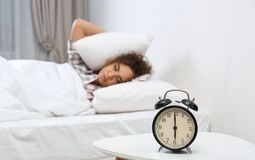 Jeune femme afro-américaine couvrant des oreilles d'oreillers tout en se cachant du réveil bedtime photo libre de droits