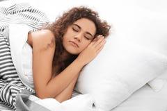 Jeune femme afro-américaine dormant sur l'oreiller mol à la maison photos stock
