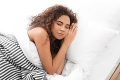 Jeune femme afro-américaine dormant sur l'oreiller mol image stock