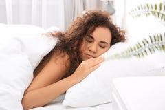 Jeune femme afro-américaine dormant sur l'oreiller mol images stock