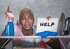 Jeune femme afro-américaine noire attirante et malheureuse sur le panneau de fer de cuisine tenant le bloc-notes avec le desper s images libres de droits