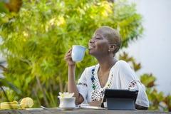 Jeune femme afro-américaine noire heureuse et attirante travaillant avec le comprimé dehors au thé potable décontracté ou au café Images stock