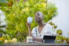 Jeune femme afro-américaine noire heureuse et attirante travaillant avec le comprimé dehors au thé potable décontracté ou au café Image stock